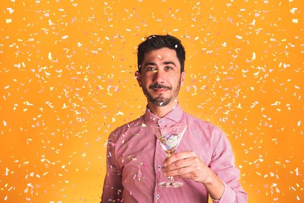Mann, der ein glas auf orange hintergrund hält