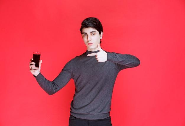 Mann, der ein glas roten saft hält und sich zufrieden fühlt