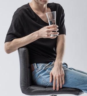 Mann, der ein glas sauberes trinkwasser hält.