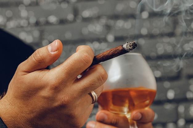 Mann, der ein glas whisky hält und zigarette in den händen nah zündet