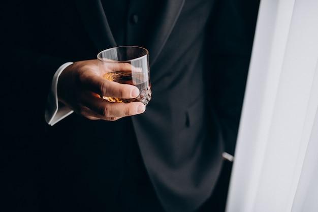 Mann, der ein glas whisky hält