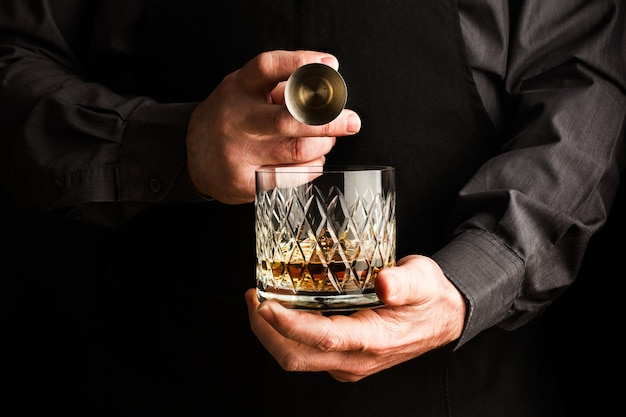 Mann, der ein glas whisky und einen barjigger hält