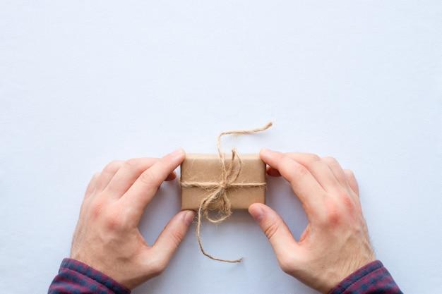 Mann, der ein handgemachtes geschenk auf einem weißen hintergrund hält