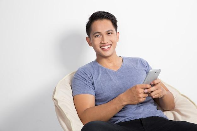 Mann, der ein handphone beim sitzen auf dem stuhl hält