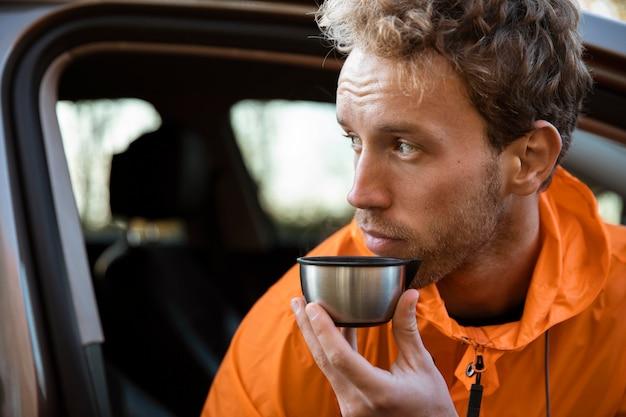 Mann, der ein heißes getränk in der tasse während auf einer straßenreise genießt