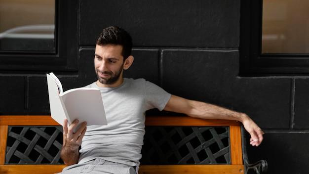 Mann, der ein interessantes buch auf einer bank liest