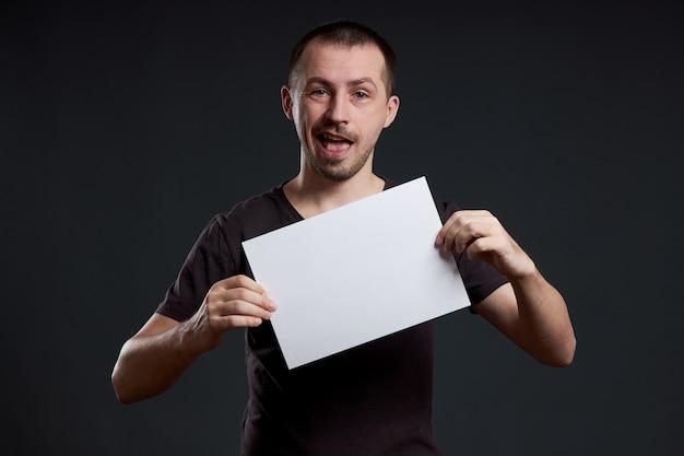 Mann, der ein leeres papierblatt in seinen händen hält