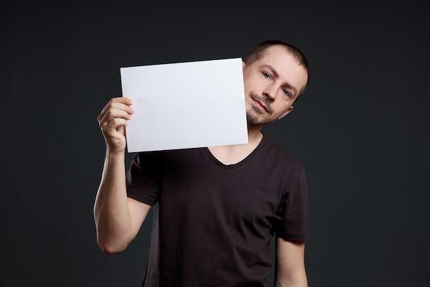 Mann, der ein leeres papierblatt in seiner hand hält