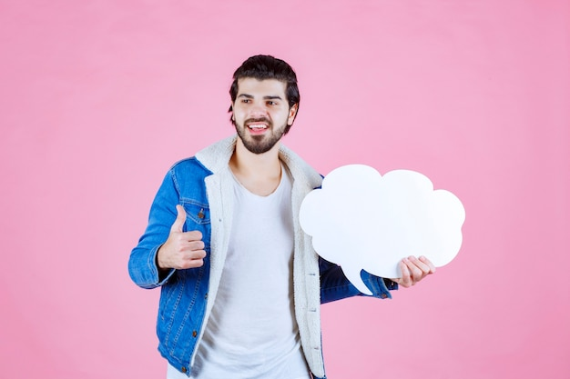 Mann, der ein leeres thinkboard in wolkenform hält und sich wie ein gewinner fühlt