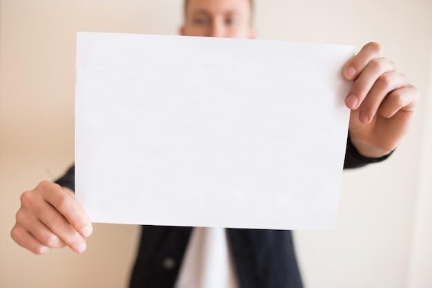 Mann, der ein leeres weißes blatt papier hält