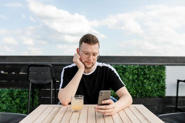 Mann, der ein mobiltelefon benutzt, während er in einem café kaffee trinkt