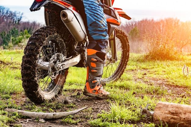 Mann, der ein motocross in einem schutzanzug im schlamm reitet