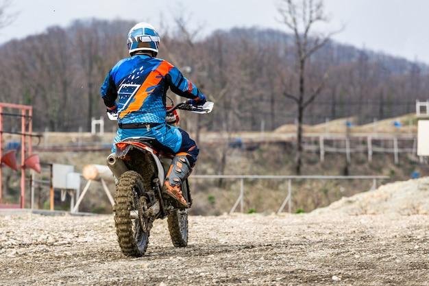 Mann, der ein motocross in einem schutzanzug reitet