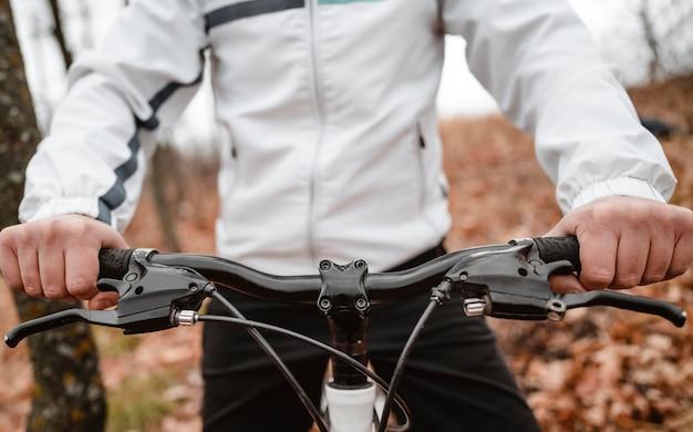 Mann, der ein mountainbike auf herbstlaub reitet
