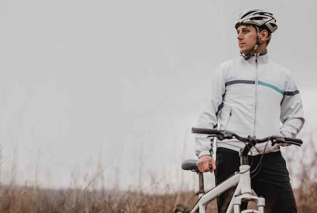 Mann, der ein mountainbike in der speziellen ausrüstung mit kopienraum reitet
