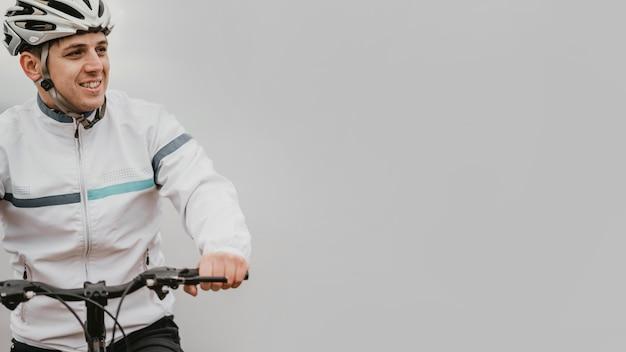Mann, der ein mountainbike mit kopienraum reitet
