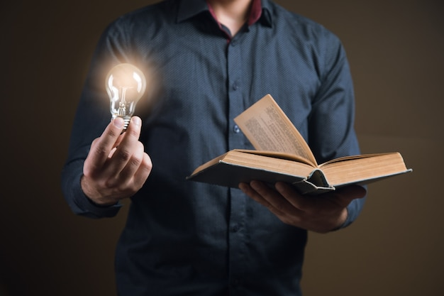Mann, der ein offenes buch und eine glühbirne hält. konzeptidee aus einem buch