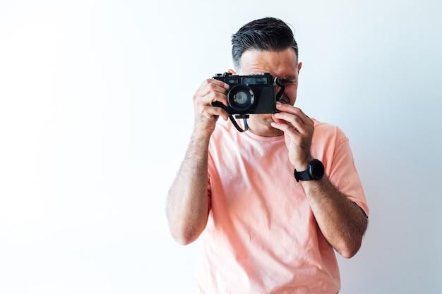 Mann, der ein rosa t-shirt trägt und ein foto mit einer alten fotomaschine macht