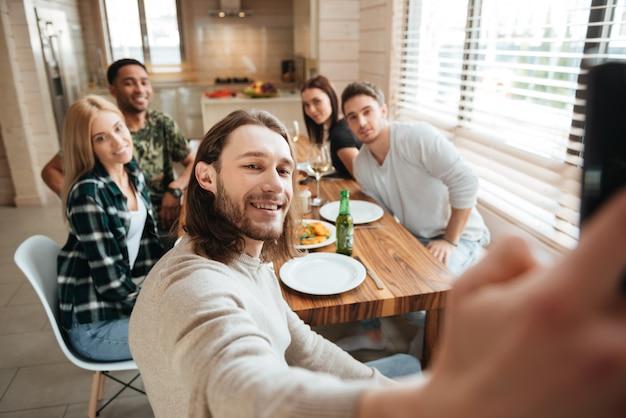 Mann, der ein selfie-foto mit freunden in der küche macht