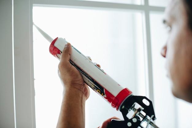 Mann, der ein silikongewehr verwendet, um ein fenster zu reparieren