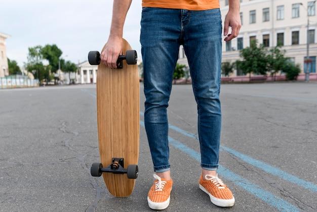 Mann, der ein skateboard auf der straße hält