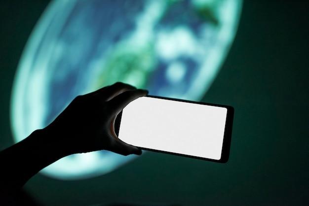 Mann, der ein smartphone am planetarium hält