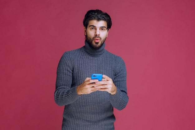 Mann, der ein smartphone hält, nachrichten liest oder sms schreibt.