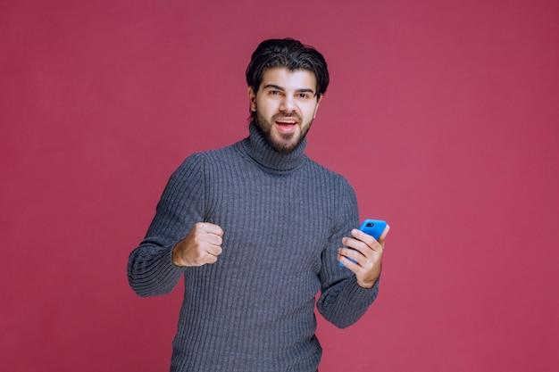 Mann, der ein smartphone hält und faust zeigt.