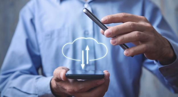 Mann, der ein smartphone mit einem cloud-computing-upload und -download hält.