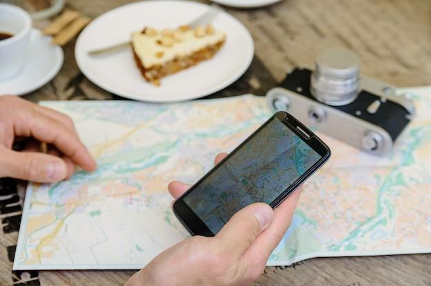 Mann, der ein smartphone nahe dort eine alte kamera, eine karte, einen kaffee und einen kuchen hält