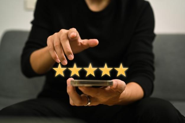 Mann, der ein smartphone verwendet und umfragen zur zufriedenheit mit positiven bewertungen gibt, die eine fünf-sterne-bewertung geben.