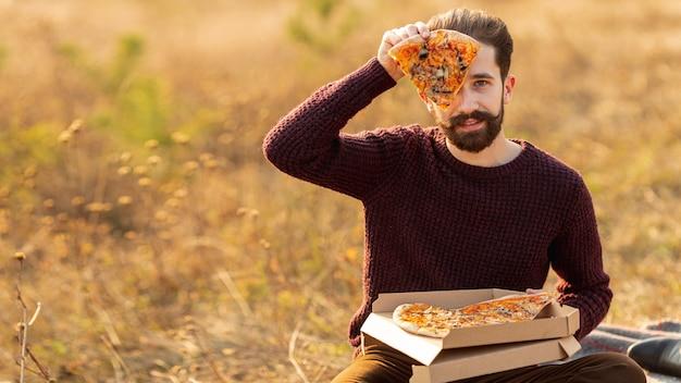 Mann, der ein stück pizza mit kopienraum zeigt