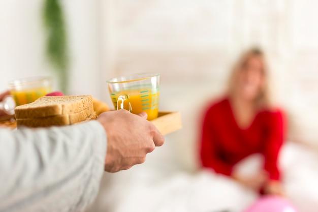 Mann, der ein überraschungsfrühstück im bett für seine freundin macht