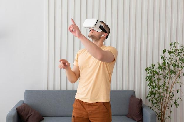 Mann, der ein videospiel spielt, während vr schutzbrillen tragen