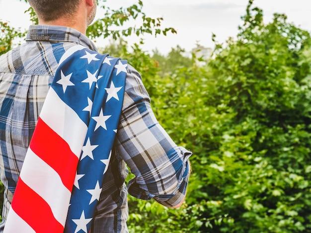 Mann, der eine amerikanische flagge hält. nationalfeiertag