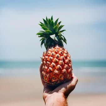 Mann, der eine ananas am strand hält