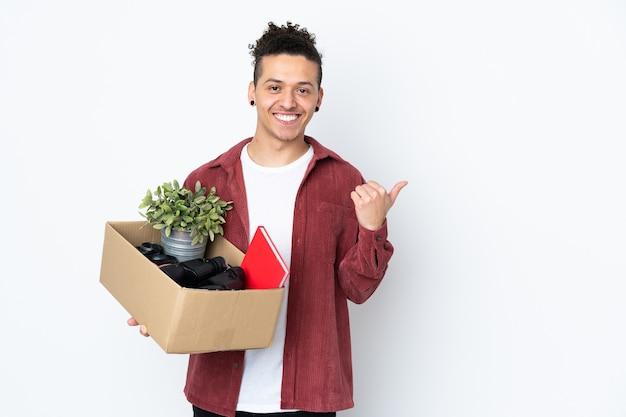 Mann, der eine bewegung macht, während er eine kiste voller dinge über isoliertem weiß aufhebt, das zur seite zeigt
