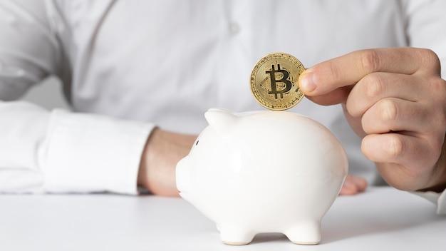 Mann, der eine bitcoin in ein sparschwein einführt