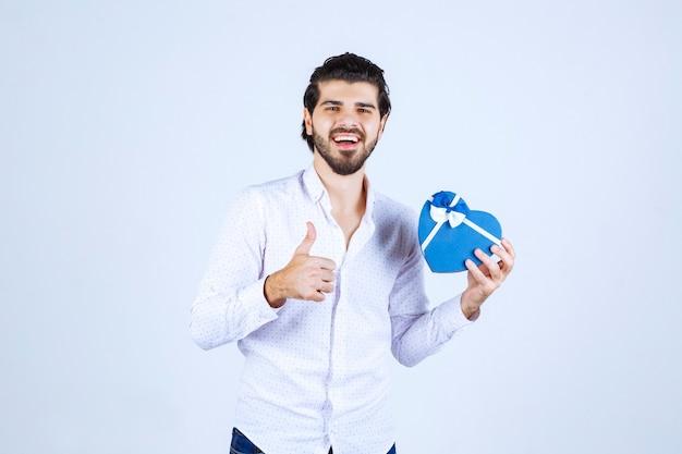 Mann, der eine blaue herzförmige geschenkbox hält und daumen nach oben zeigt