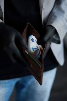 Mann, der eine brieftasche mit geld euro in der hand in schwarzen medizinischen handschuhen hält. geld sparen. die weltkrise