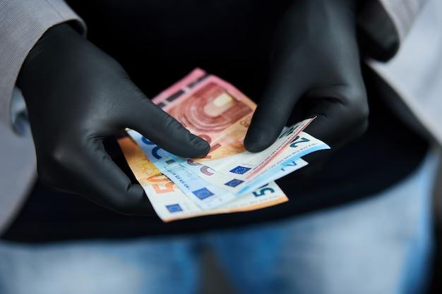 Mann, der eine brieftasche mit geld euro in der hand in schwarzen medizinischen handschuhen hält