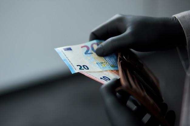 Mann, der eine brieftasche mit geld euro in der hand in schwarzen medizinischen handschuhen hält.