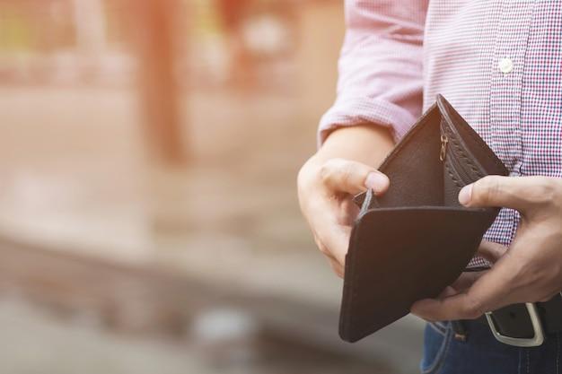 Mann, der eine brieftasche mit geld hält