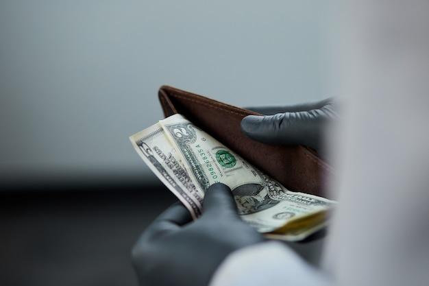 Mann, der eine brieftasche mit gelddollar in der hand in schwarzen medizinischen handschuhen hält. coronavirus krise. geld sparen. kein mann.