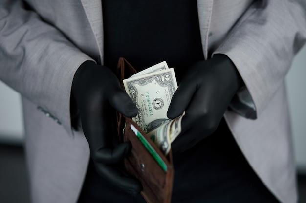 Mann, der eine brieftasche mit gelddollar in der hand in schwarzen medizinischen handschuhen hält. geld sparen. kein geld. die weltkrise