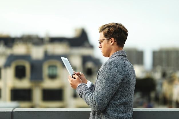 Mann, der eine digitale tablette an einer dachspitze in san francisco verwendet