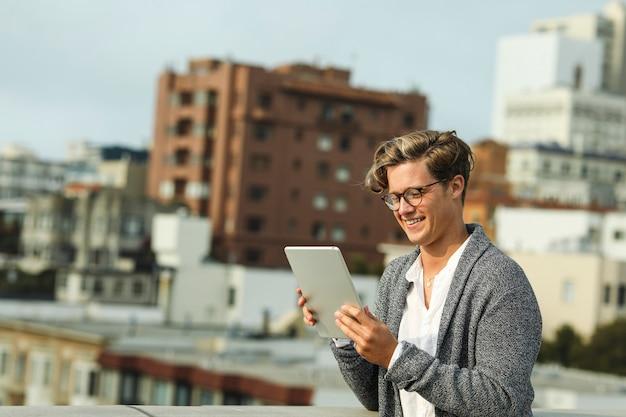 Mann, der eine digitale tablette auf einer dachspitze in san francisco verwendet