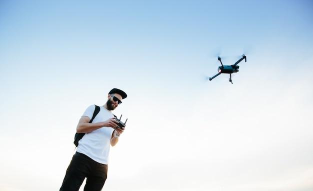 Mann, der eine drohne über einen controller steuert und fliegt. mann spielt mit der drohne