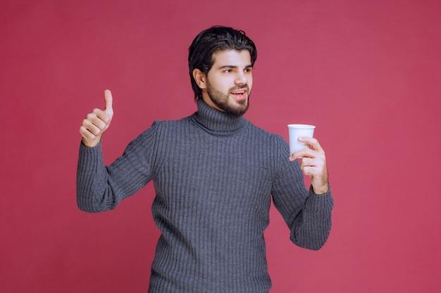 Mann, der eine einwegkaffeetasse hält und genusszeichen macht. Kostenlose Fotos