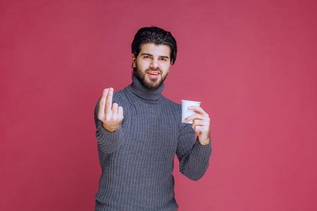 Mann, der eine einwegkaffeetasse hält und genusszeichen macht.
